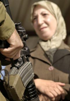 A Palestinian woman waits to pass through an Israeli checkpoint in the occupied West Bank (Rusty Stewart)