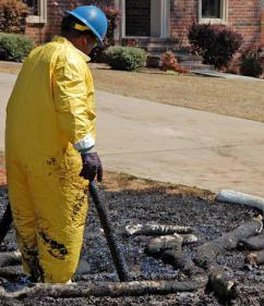 Cleanup workers try to remove oil from a front yard in Arkansas