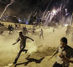 Palestinians in the West Bank run from an Israeli bombardment of tear gas  (Kelly Lynn)