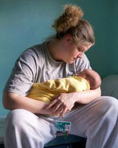 An incarcerated mother holds her infant child inside her prison cell