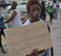 A protester in Ferguson calls for Mike Brown's murderer to be arrested