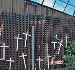 A section of the border wall in Nogales, Ariz., with crosses and names of people who died attempting to cross. (Eric Ruder | SW)