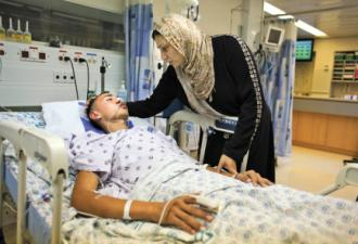 Jamal Julani lies in a hospital bed after being beaten and left for dead