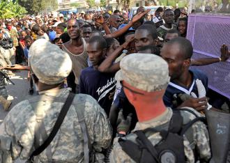 U.S. soldiers hold back a large gathering of displaced people waiting for aid in Port-au-Prince (Master Sgt. Jeremy Lock)