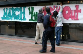 Activists post a banner for the March 4 Day of Action at Laney College in Oakland (TheBlackHour.com)