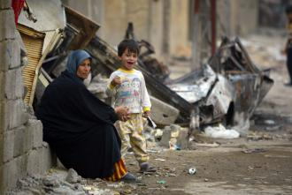 An Iraqi mother and her son sit amid the rubble