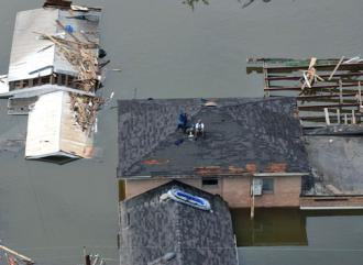 Stranded New Orleans residents sit on their roof in the wake of the Katrina disaster (Jocelyn Augustino)