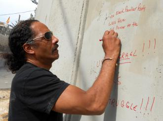 Aaron Dixon, a delegation participant, leaves a message of solidarity on the Israeli apartheid wall