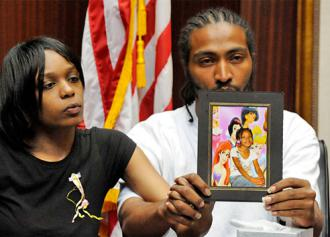 Aiyana Jones' parents hold up her picture at a press conference