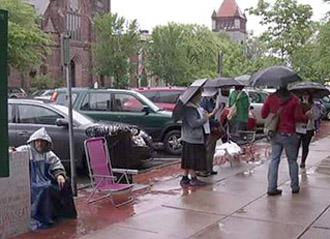 Picketing in the rain against the removal of downtown benches in Northampton, Mass.