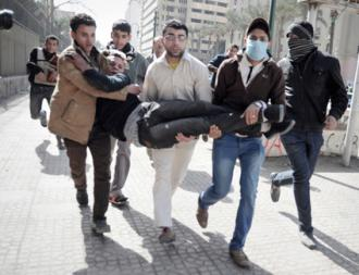 Protesters rush a wounded man away from clashes with armed forces in Cairo