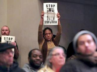 Protesters stand against William Bratton during an Oakland City Council meeting