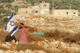 An Israeli girl walks past an illegal outpost of the Jewish settlement of Avnei Hefetz in the West Bank (Gili Yaari)
