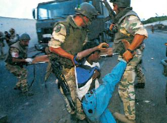 Italian troops drag away a Somali civilian wounded in U.S.-led bombing