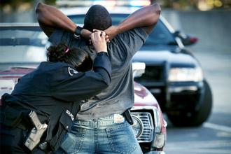 A New York City police officer searches a young Black man