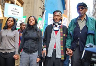 Rev. Herbert Daughtry (second from right) stands with fellow protesters to defend the day care center he founded