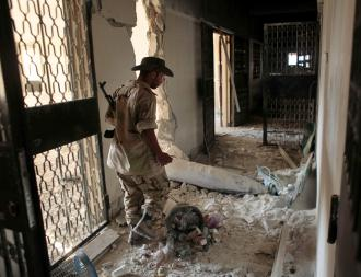 A Libyan rebel in Zawiyah guards an unexploded NATO bomb (Etienne De Malglaive | ABACA Press)