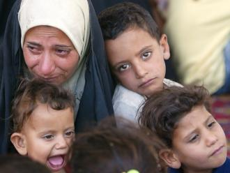 An Iraqi woman and her children in the district of Hor Rejab in southwestern Baghdad (Ahmad Al-Rubaye | AFP)