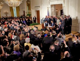 Barack Obama signs health care legislation in front of Democratic lawmakers in the East Room of the White House (Lawrence Jackson)