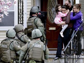 Heavily armed police search a family's home in locked-down Boston