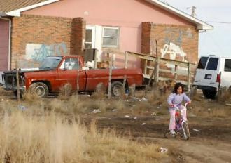 A girl plays outside her home on an American Indian reservation