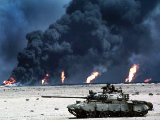 A U.S. tank rolls by a burning oil field in Iraq