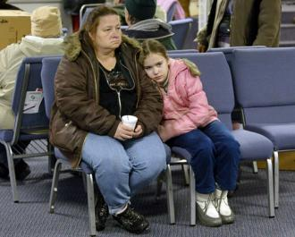 A mother and daughter wait for help at a government office