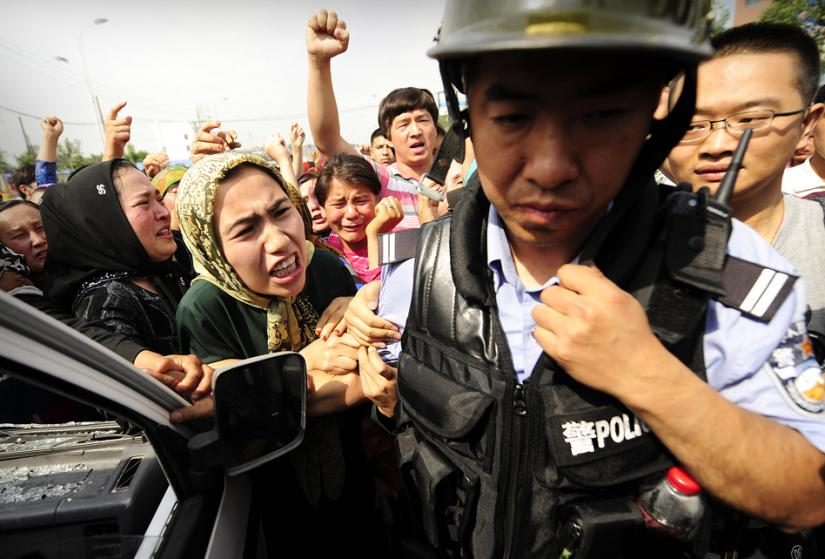 Uighur women protesters challenge Chinese riot police during demonstrations in western Xinjiang province