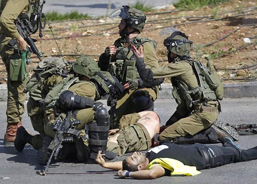 Israeli soldiers surround the body of the Palestinian man they shot