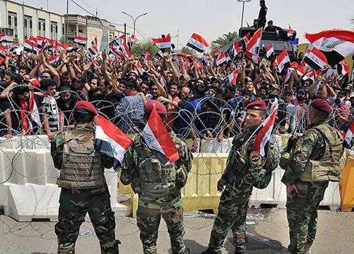 Masses of protesters confront Iraqi troops at the boundaries of the Green Zone in Baghdad