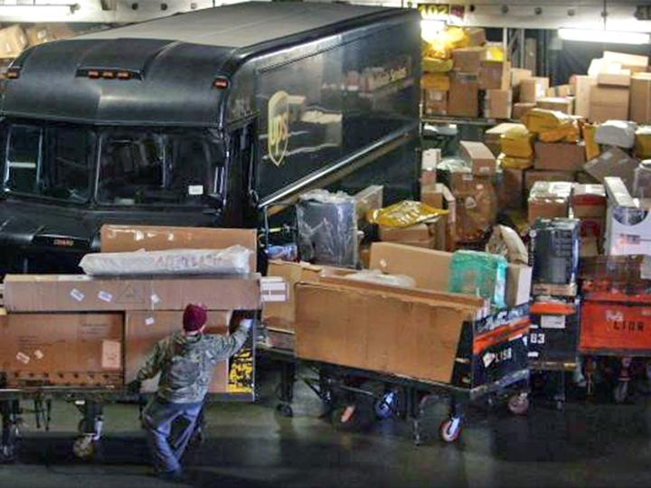 A UPS employee loads packages at a regional hub in Ontario, California