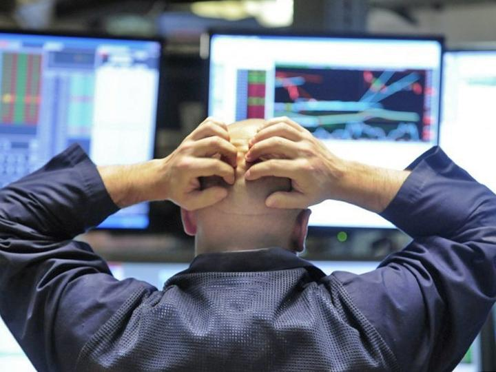 A financial trader looks on as stock prices collapse