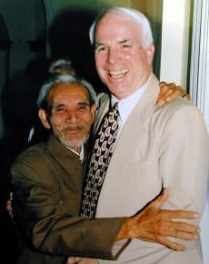 John McCain hugs his rescuer Mai Van On at a meeting in 1996