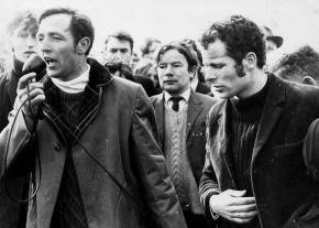 Civil rights organizer Eamonn Melaugh speaks at a housing rally in Derry as Eamonn McCann (right) looks on