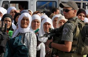 An Israeli soldier stands guard over Palestinians waiting to cross at a checkpoint