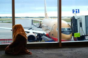 A Muslim woman prays in an airport