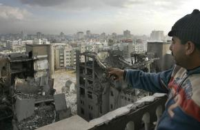 A man looks out over the wreckage left by Israeli air strikes in Gaza City