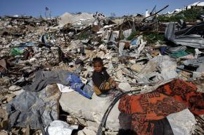 A young boy sits amid the rubble where buildings once stood in Jabalia, a town in the northern Gaza Strip