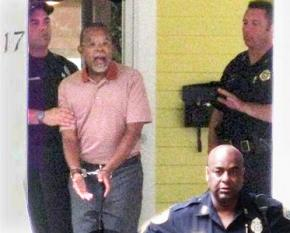 A photo, taken by a neighbor, of Black scholar Henry Louis Gates led out of his own home in handcuffs