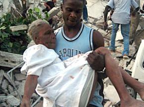 A man carries an injured woman from the rubble after the earthquake in Port-au-Prince