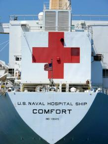 A U.S. Navy ship bearing the Red Cross logo
