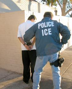 An ICE agent detains an undocumented worker