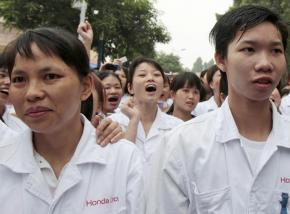 Strikers march outside the shut down Honda motor factory in Zhongshan, Guangdong province