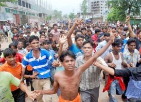 Striking garment workers who gathered to protest low wages flee police firing tear gas and rubber bullets