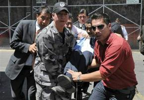 Ecuador's President Rafael Correa is taken away after being overcome by tear gas