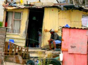 A man sits outside a makeshift home in a slum in Cape Town, South Africa