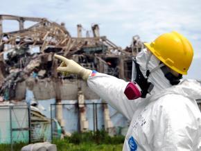 Inspectors survey the damage at one of the Fukushima-Daiichi nuclear plant's reactors