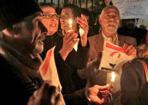 Demonstrators gather for a vigil following the burning of a Coptic church in Cairo