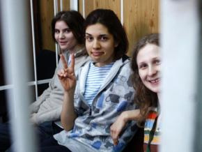 Members of Pussy Riot sit in the cage where they were confined during their trial