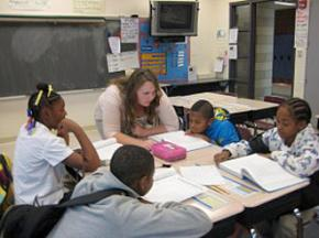 A teacher works with students in her fifth-grade class